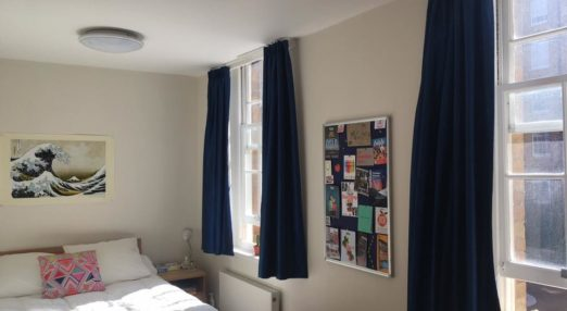 A student bedroom with navy curtains and a bed with white covers