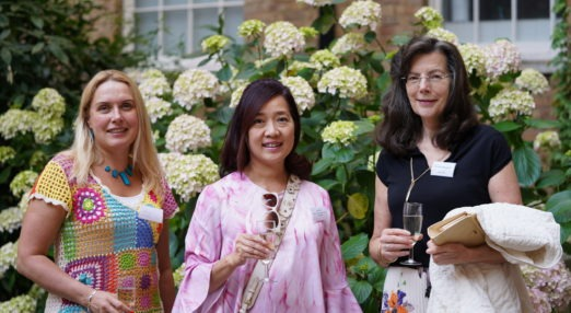 Three Goodenough College Alumni women with champagne glasses in front of flowers