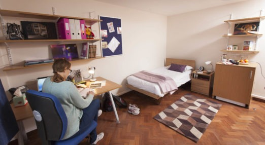 Member reading in her room at Goodenough College